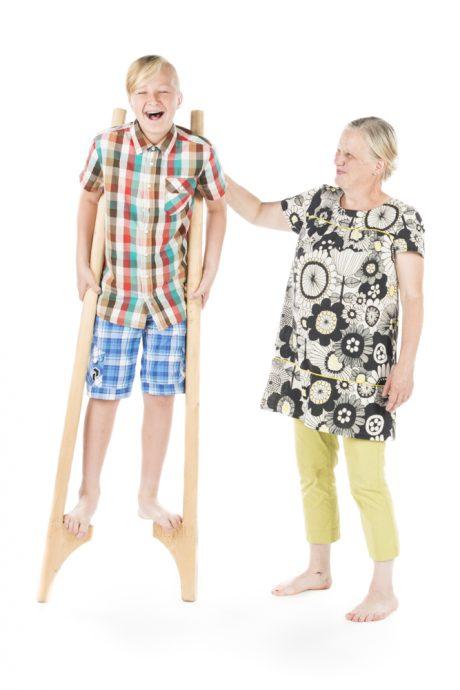 isoäiti opastaa lapsenlasta kävelemään puujaloilla